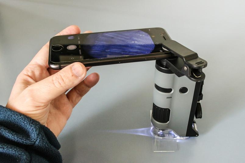 Bild eines Kleinmikroskops, an das ein Smartphone angeschlossen ist.