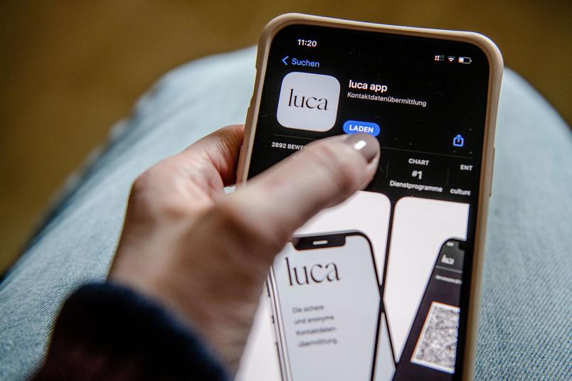 Eine Person tippt auf dem Smartphone auf den Herunterladen-Button.