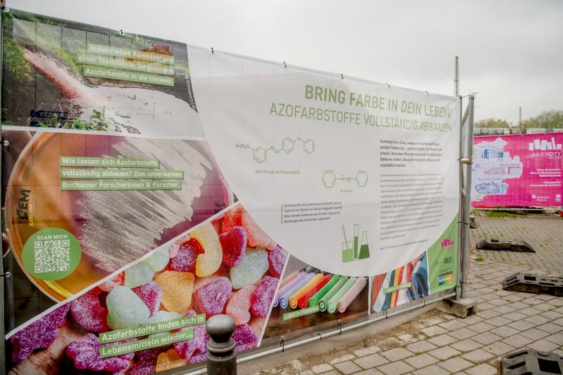 <div> Das Bochumer Bauzaunbanner informiert über die Forschung an der RUB zum Abbau von Azofarbstoffen.</div>