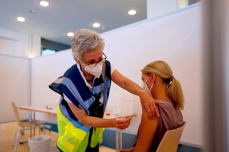 Betriebsärztin Dr. Kirsten Wiegand impft eine der freiwilligen Helferinnen.