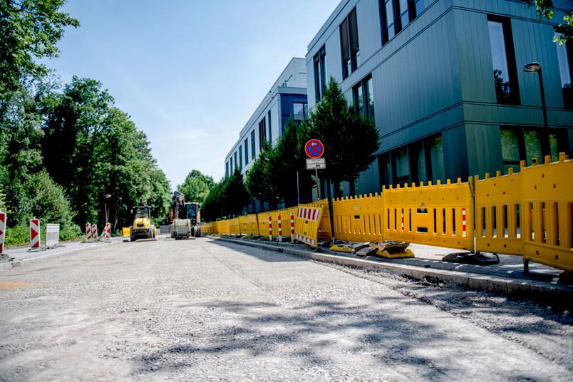 Die Asphaltdecke einer Straße ist abgetragen, im Hintergrund stehen Baufahrzeuge.