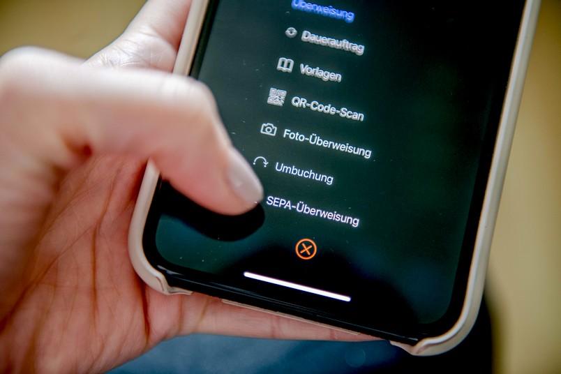Nahaufnahme eines Smartphones, das eine Person in der Hand hält, um eine Überweisung zu tätigen