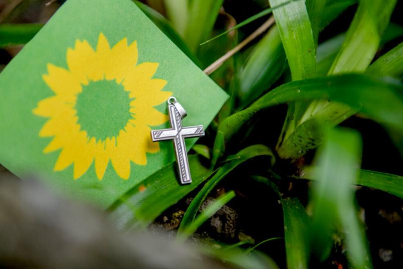 Christliches Kreuz und Logo der Grünen