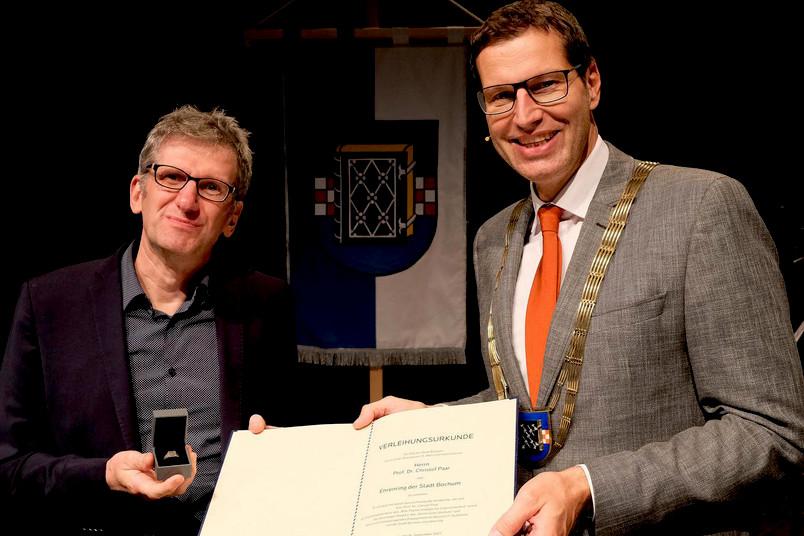 Oberbürgermeister Thomas Eiskirch (rechts) übergibt den Ehrenring an Christof Paar.