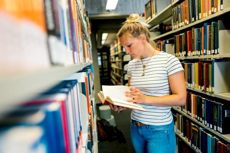 Studentin zwischen Bücherregalen