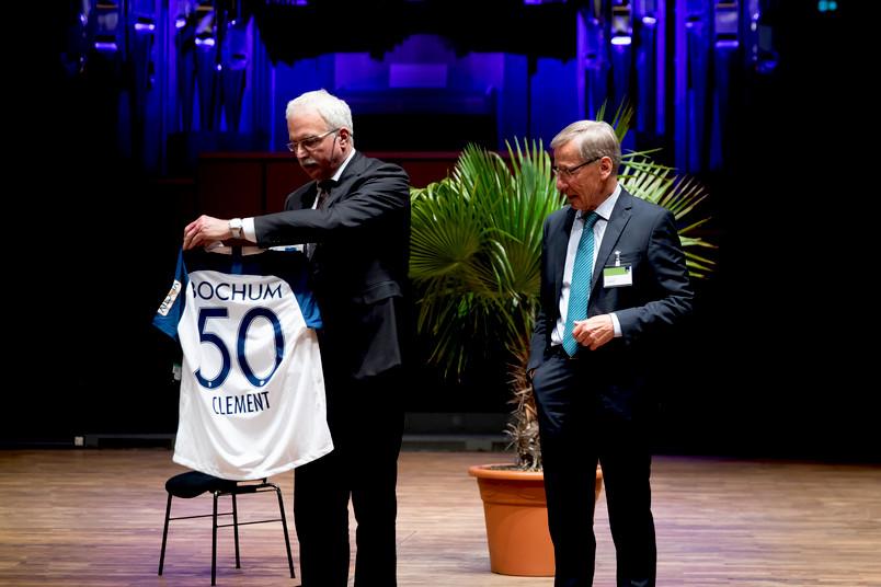 Ein Trikot mit der Rückennummer 50 von seinem Lieblingsverein VfL Bochum hat der ehemalige NRW-Ministerpräsident Wolfgang Clement (rechts) von Medizin-Dekan Ralf Gold überreicht bekommen.