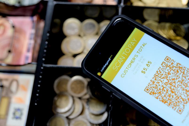 Kasse mit Euro-Müzen, auf dem ein Handy mit Bezahldisplay liegt