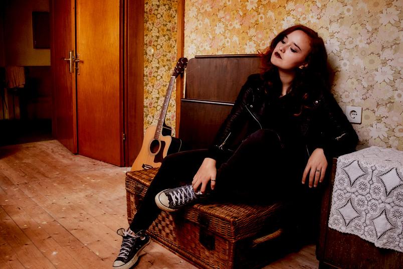 Sängerin mit Gitarre auf Sofa