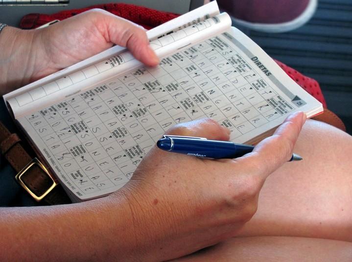 Eine Frau sitzt auf einem Stuhl und löst ein Kreitzworträtsel.