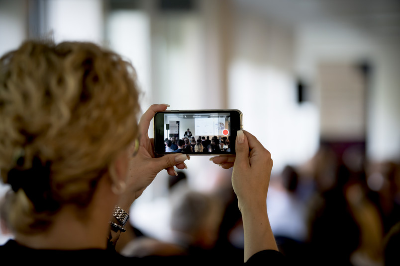 Foto von einem Handy, mit dem jemand einen Vortrag filmt