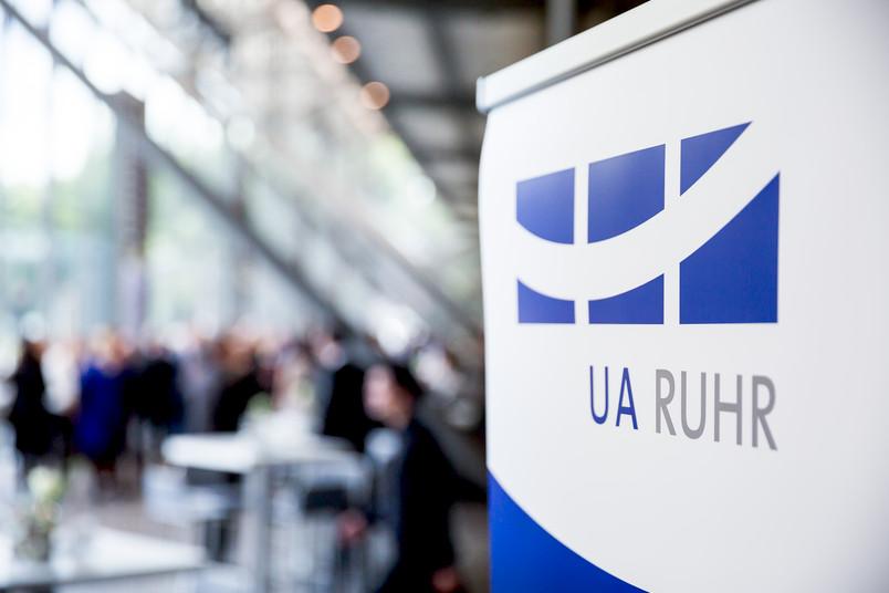 Das Logo der Universitätsallianz Ruhr in der Jahrhunderthalle. Im Hintergrund sind verschwommen Gäste zu sehen.