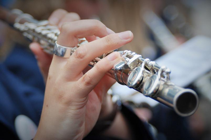 Nahaufnahme einer Frau, die Querflöte spielt. Zu sehen sind ihre Hand und das Instrument.