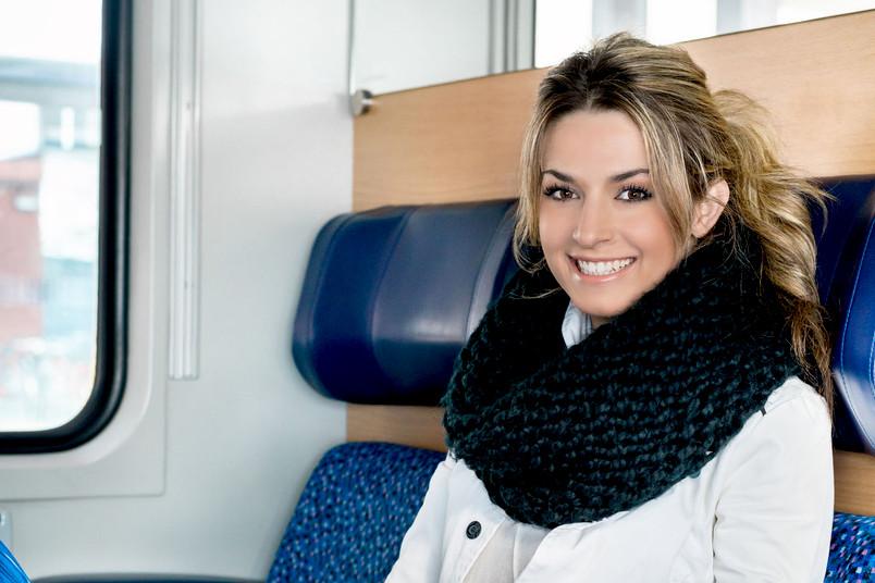 Junge Frau sitzt im Zug.