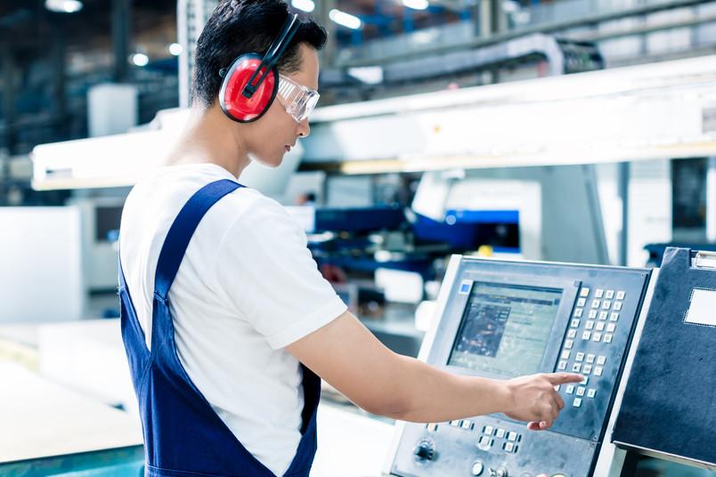 Ein Arbeiter gibt Daten an einer CNC-Maschine in einer Produktionshalle ein
