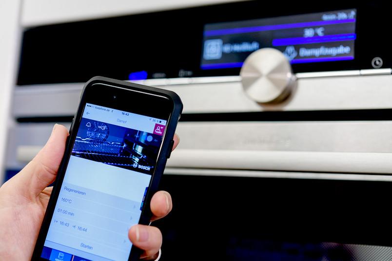 Eine Hand hält ein Smartphone vor einen Ofen. Auf dem Display sind diverse Einstellmöglichkeiten für das Gerät zu sehen.