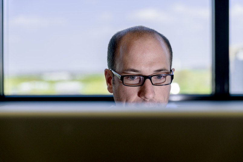 Der Kopf eines Forschers ragt hinter einem Computermonitor hervor.