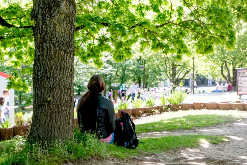 Studentin sitzt auf einer Wiese.