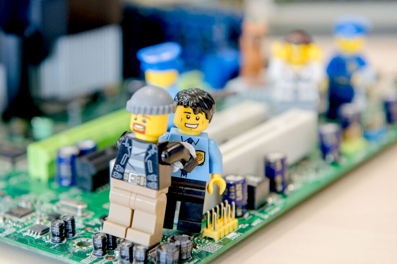Ein Polizisten-Lego-Männchen nimmt ein Gauner-Lego-Männchen fest, während sie auf einer Computerplatine stehen.