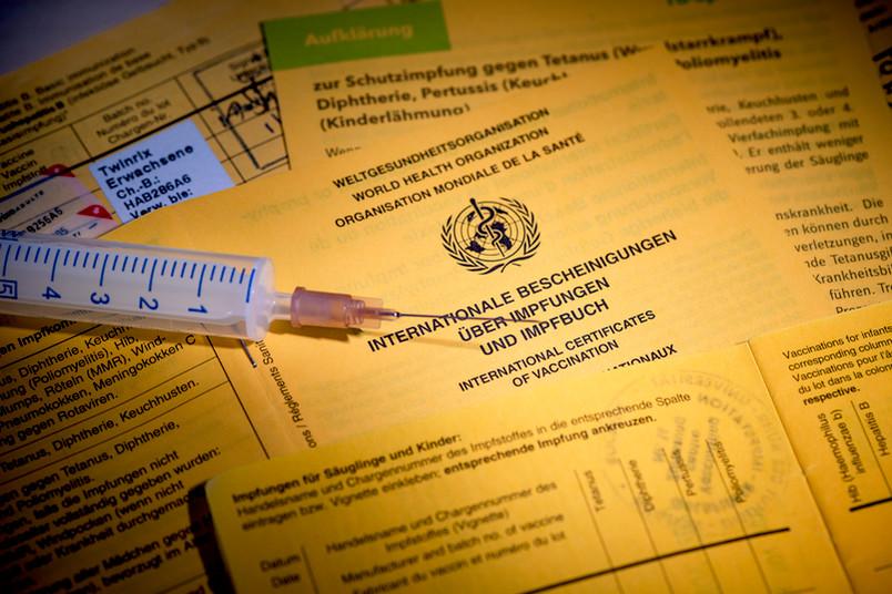 Spritze auf einem Impfausweis