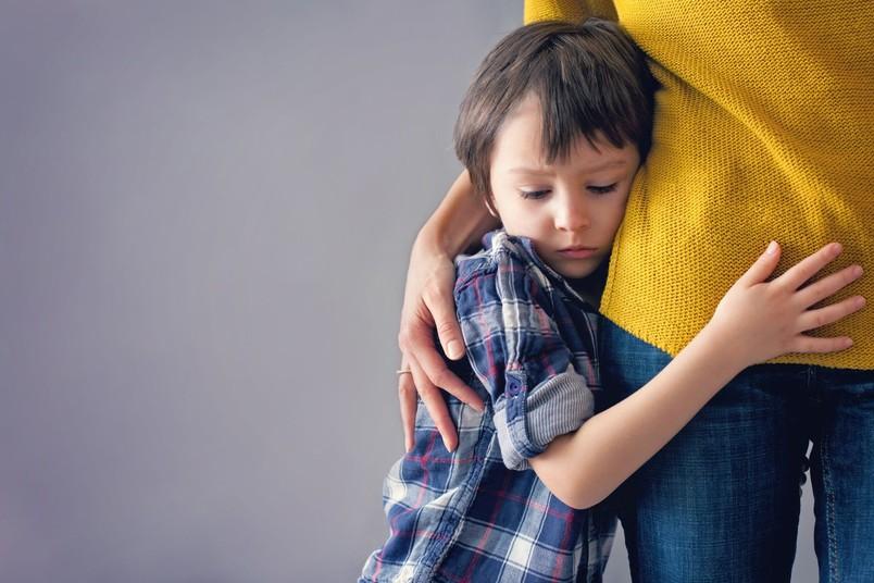 Ein Kind drückt sich ängstlich an seine Mutter