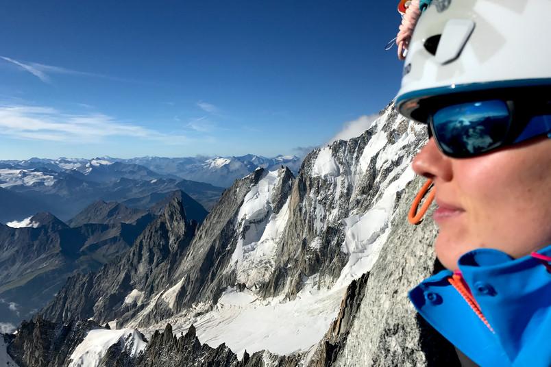 Bergsteigerin blickt von einem Berg ins Tal.
