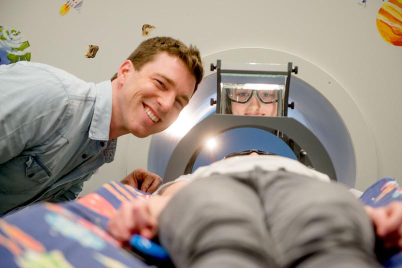Kind mit Forscher im Kernspinraum