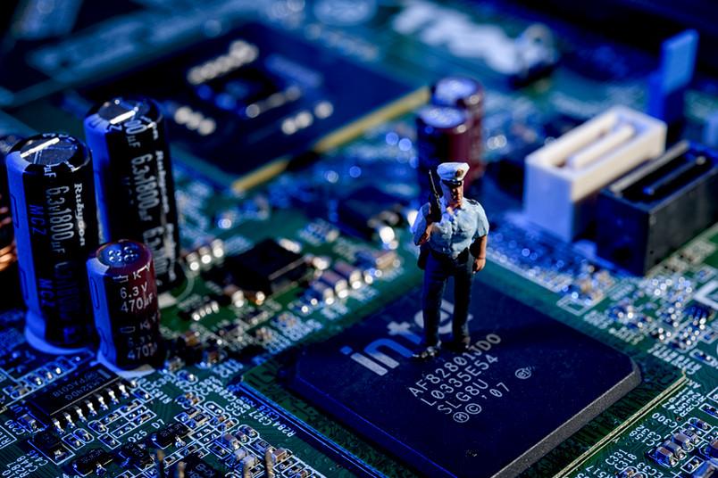 Blick auf einen Computerchip, auf dem ein Polizisten-Modellmännchen steht.