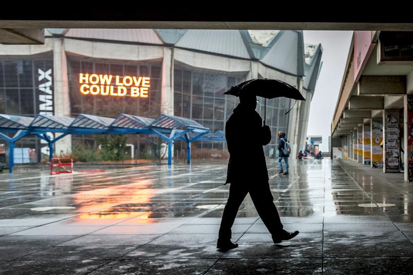 Mann läuft mit Regenschirm über den RUB-Campus.