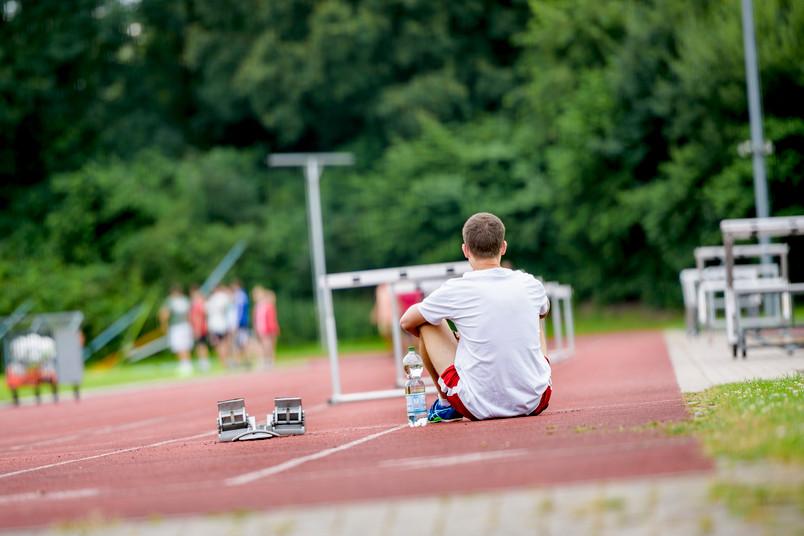 Sportler sitzt auf einer Tartanbahn.