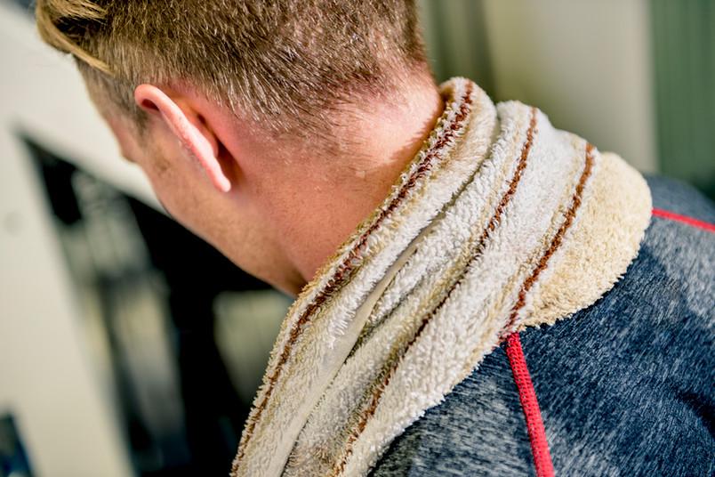 Verschwitzter Sportler mit einem Handtuch im Nacken.