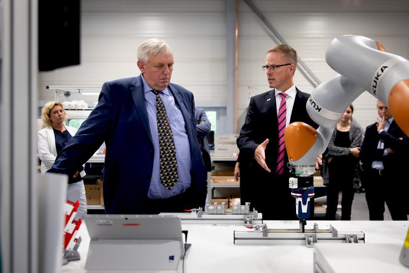 NRW-Arbeitsminister Karl-Josef Laumann (links) besucht die Bochumer Lern- und Forschungsfabrik. Was der Roboterarm macht, erläutert Bernd Kuhlenkötter.