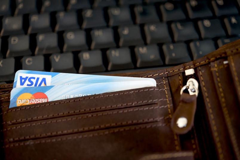 Ein Portemonnaie mit Kreditkarten liegt auf einer Computertastatur.