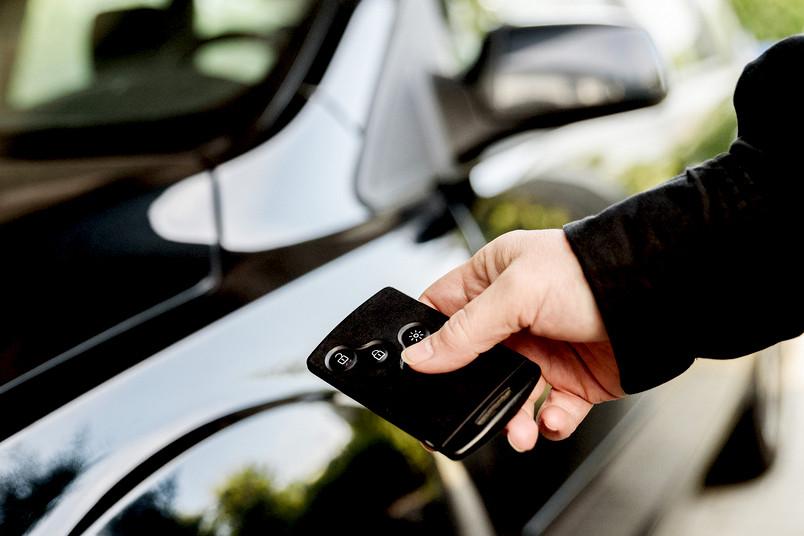 Eine Hand betätigt einen elektronischen Autoschlüssel. Im Hintergrund ist ein Auto zu sehen.