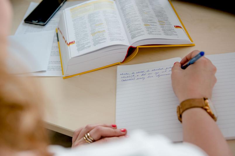 Eine Hand schreibt Text auf Papier.