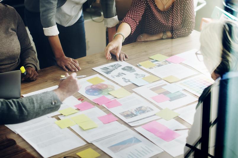 Arbeitssituation mit Papieren und Post-its an einem großen Tisch