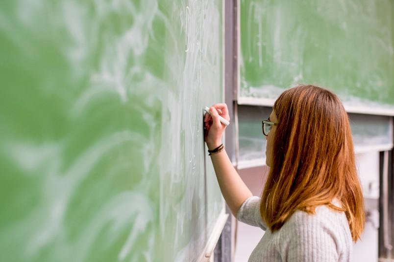 Studentin schreibt an eine Tafel.