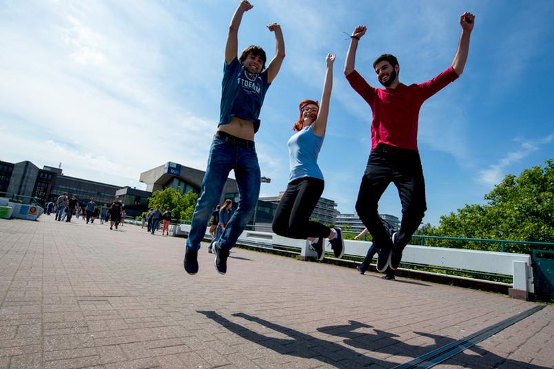 Studenten springen vor Freude in die Luft, im Hintergrund ist der Campus der Ruhr-Universität Bochum zu sehen