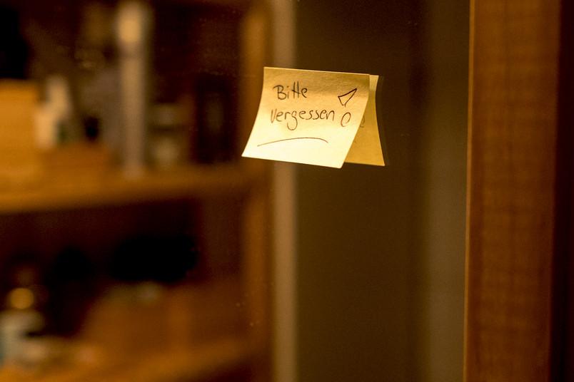 """Post-it mit der Aufschrift """"Bitte vergessen"""" an einem Spiegel"""