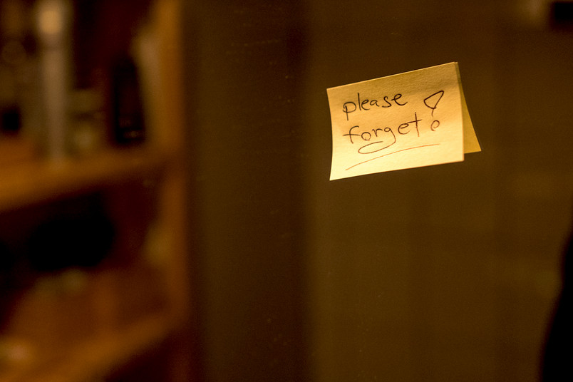 "Piece of paper with inscription ""Please forget"" on a mirror"