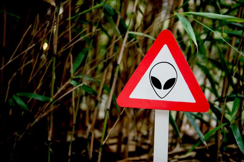 Warnschild mit einem Alien-Kopf