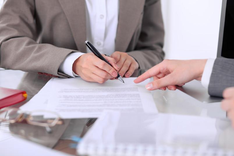 Zwei Menschen arbeiten zusammen an einem Dokument.