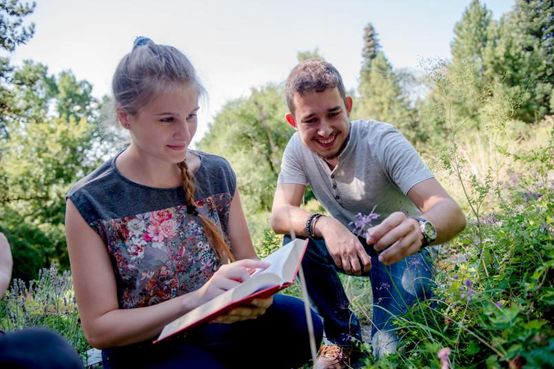 Zwei Studierende schauen sich Blumen auf einer Wiese an.