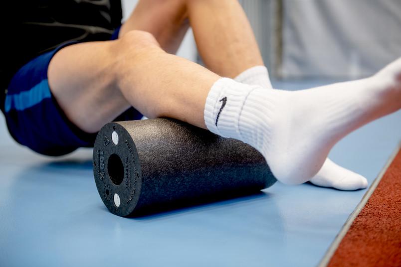 Sportler rollt Bein über eine Blackroll.