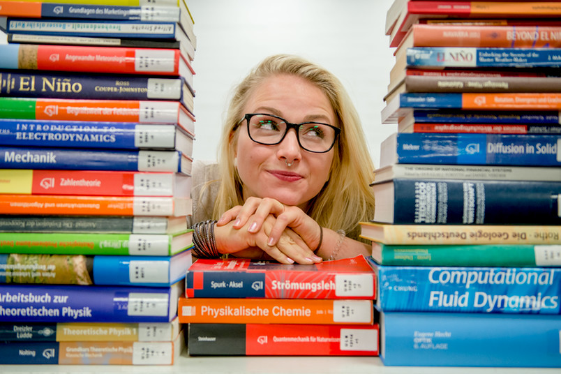 Studentin schaut durch einen Stapel Bücher.