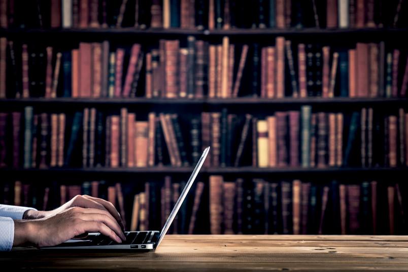 Mann am Laptop vor einer Bücherwand in der Bibliothek