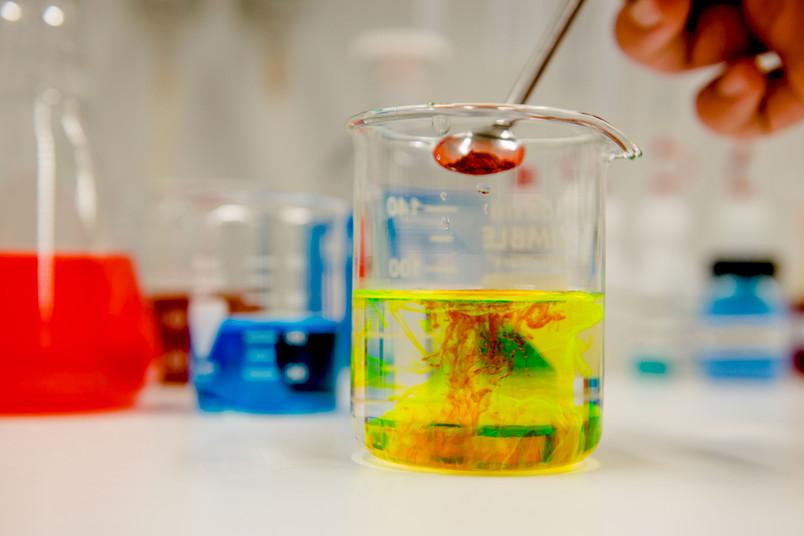 Ein Pulver rieselt von einem Löffel in ein Gefäß mit einer bunten Flüssigkeit.