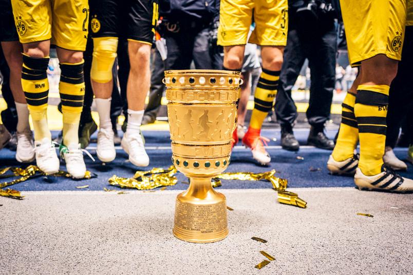 Der DFB-Pokal beim Finalspiel in Berlin – im Hintergrund Beine der Spieler von Borussia Dortmund