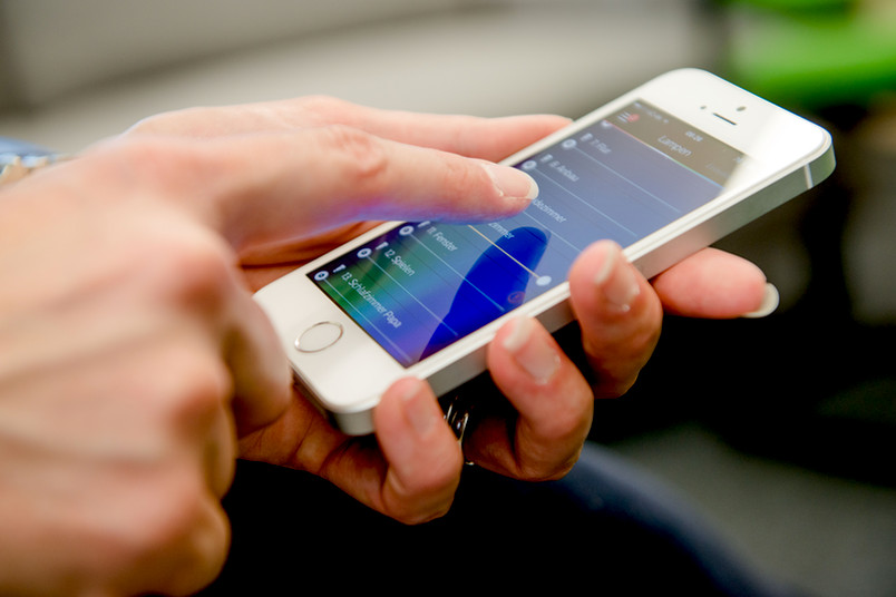 User hält mobiles Gerät in der Hand und bedient es.