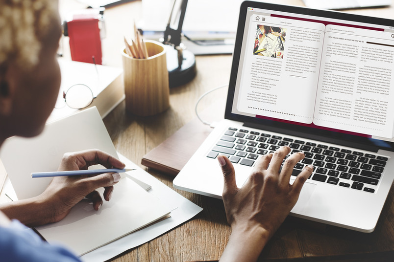 Eine Person sitzt vor einem Laptop und arbeitet mit einem elektronischen Dokument
