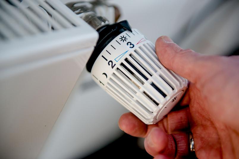 Hand an einer Heizung regelt die Temperatur